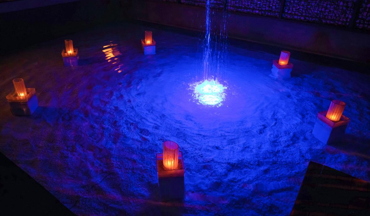 青い光でライトアップされた水面が幻想的なエントランスのイメージ